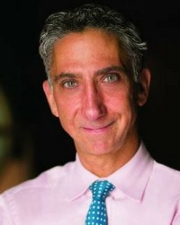 Portrait of a man wearing a pink shirt and a blue tie