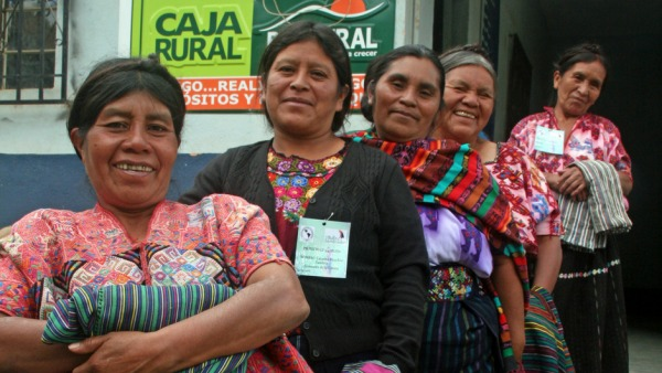 A group of five women wearing colorful traditional clothing and smiling at the camera