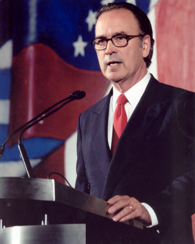A man wearing a red tie and suit speaking into a microphone at a lectern
