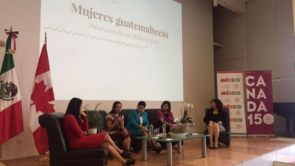 Five women sitting on a stage with Mujeres guatemaleeas on a screen behind them and the Mexican and Canadian flags