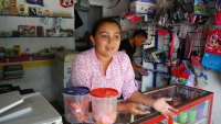 A woman stands behind the counter at a small shop selling various items like bags and pencils