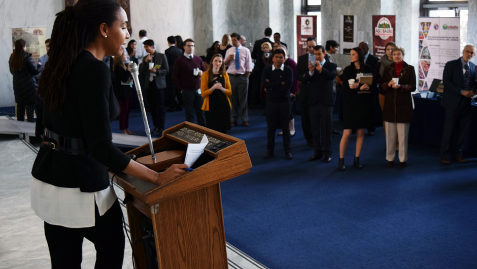 A woman stands at a podium speaking into a microphone to a crowd of people looking on