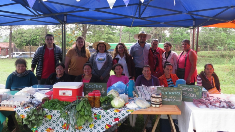 a group of people standing behind a table filled with produce under a tent outside
