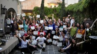 A large group of women pose together in a courtyard some with their arms raised in the air and some holding certificates