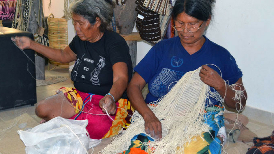 Two old women sitting on the floor weaving