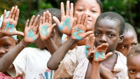 A group of children with their palms facing the camera with the word Magazen written on their palms in blue paint