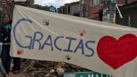 A woman holding up painted sign saying Gracias with a red heart and handprints