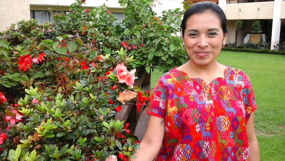 A woman in a colorful top stands next to a flower bush in a garden and smiles at the camera