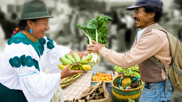 Man handing a woman in traditional clothes a bunch of greens and the woman is handing the man a bunch of bananas