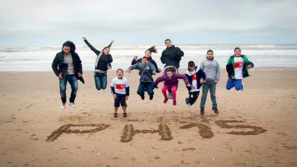 A group of children on a beach with the water behind them jumping in the air with PH15 written in the sand in front of them