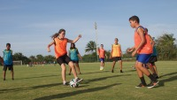 A girl with a soccer ball and a boy coming towards her with other children behind them on the field