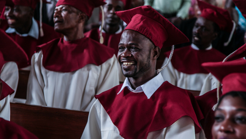 A man wearing graduation cap and gown smiles in the crowd