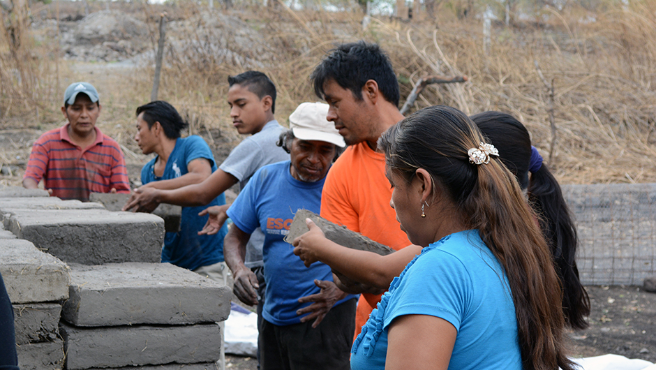 A group of men and women work together to create a building foundation by stacking large cement blocks
