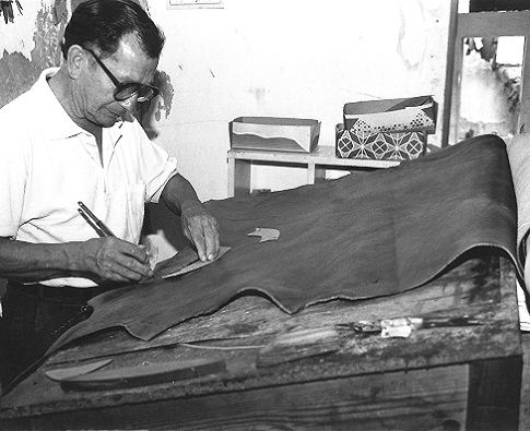 A member of CESAP in his workshop cuts leather to make shoes.