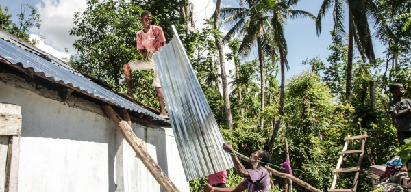 Two Haitian men lift tin on a roof