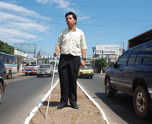 A blind member of Saraki stands independently on the median of a busy street.