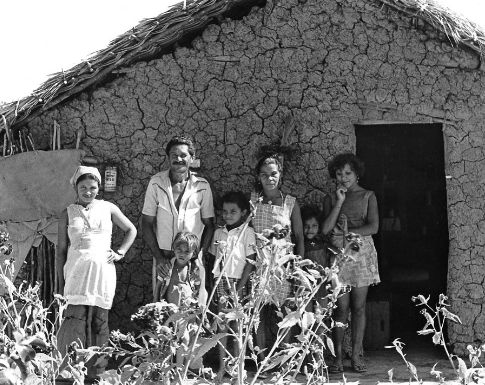 A family stands in front of their home in rural Brazil