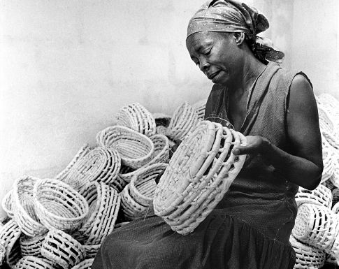 A Haitian woman making baskets from banana bark and white palm