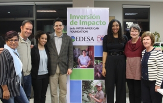 IAF and EDESA staff gather in front of a sign celebrating the launch of the IAF's first impact investment.