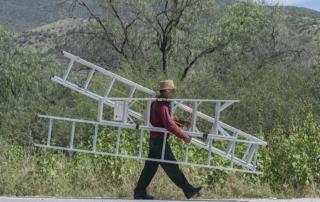 Un emprendedor centroamericano lleva tres escaleras a su siguiente trabajo