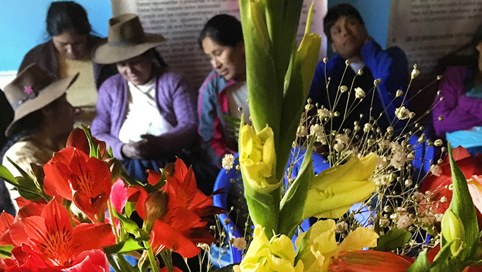 Members of ASPROFLOR, an IAF grantee partner, talk amongst themselves behind a bouquet of vibrant flowers.
