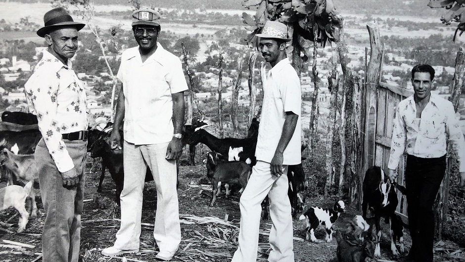 IAF Grantees in Action: Four men dressed in light colors stand near farm animals in rural Dominican Republic
