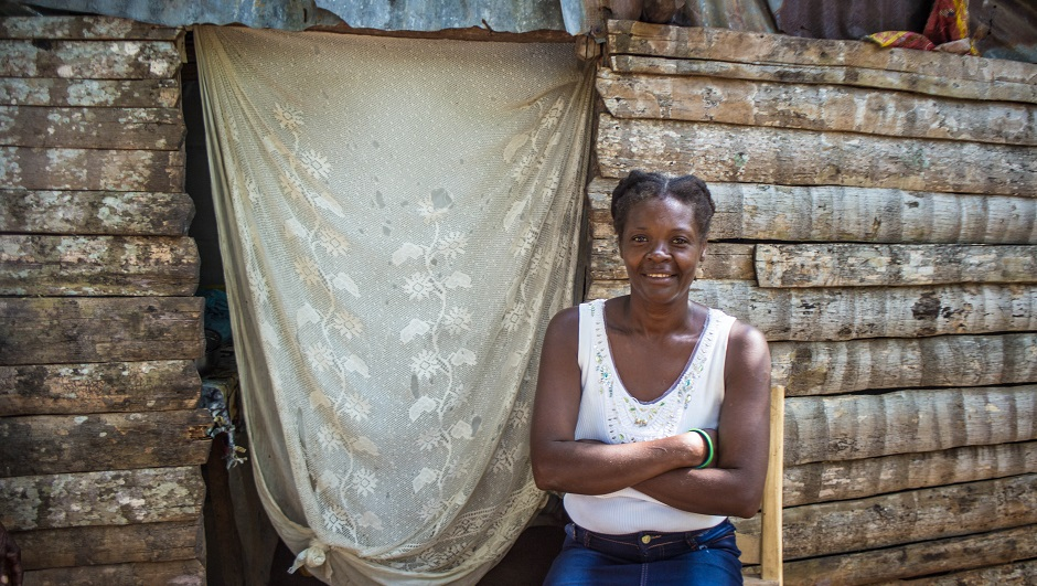 A smiling Haitian woman stands next to the doorway of her home.