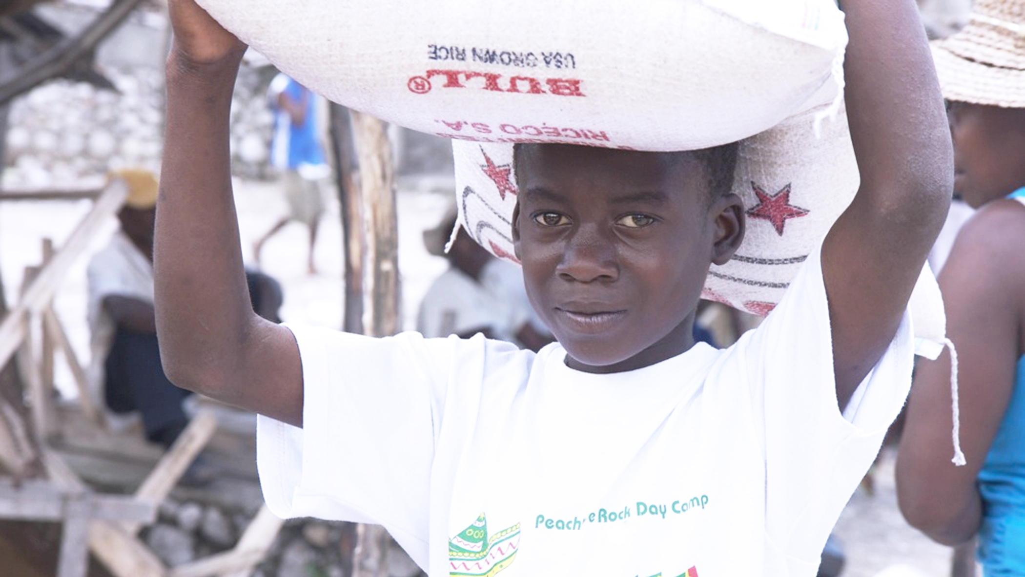 A member of MP3K carries a large bag of rice on his head.