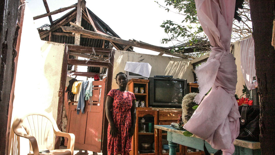 After Hurricane Matthew, a Haitian project participant stands within her home where her roof has been blown off.