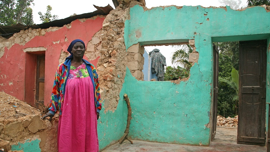 A Caribbean woman stands proudly inside her battered home after a hurricane.