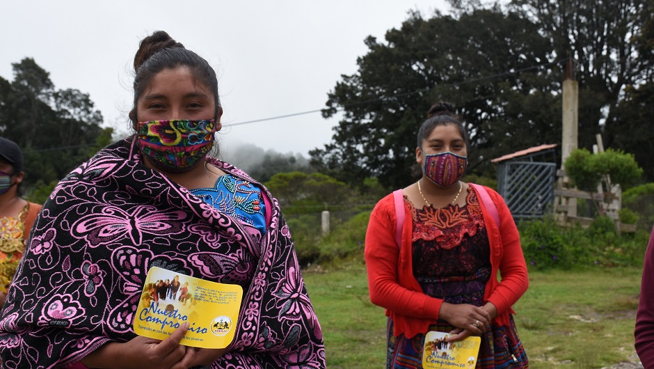 Two young Guatemalan women in masks stand with dignity.