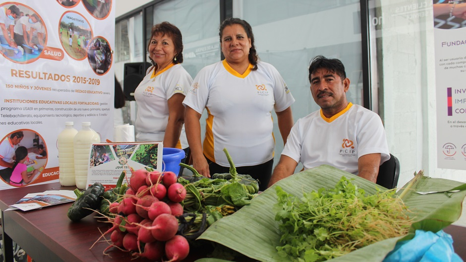 Three members of a Mexican community foundation stand next to a table at an indoor fair. Their table displays freshly picked vegetables and posters showing their postive impact in the community.