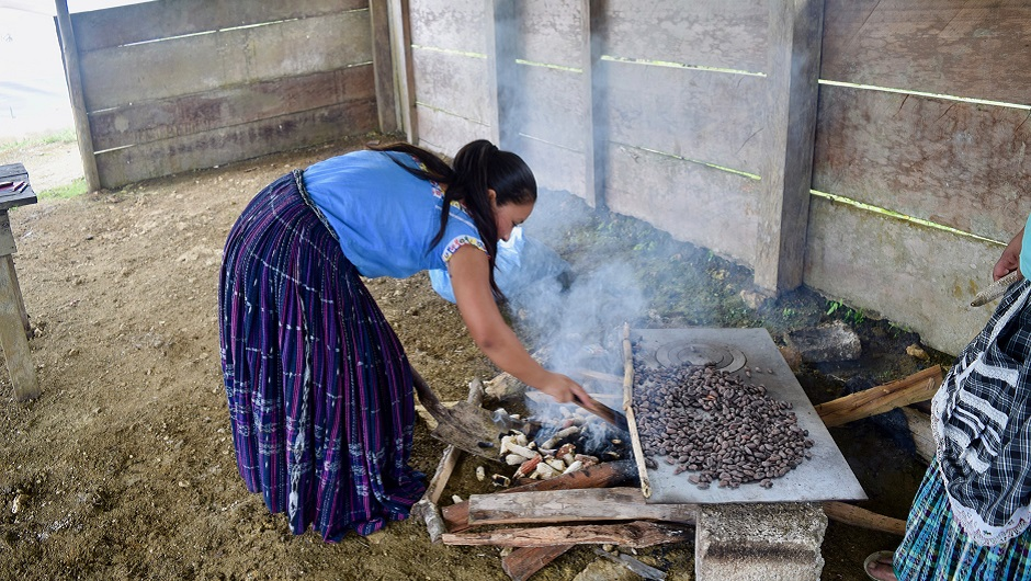 A Guatemalan woman in a traditional skirt roasts coffee beans over an open fire.