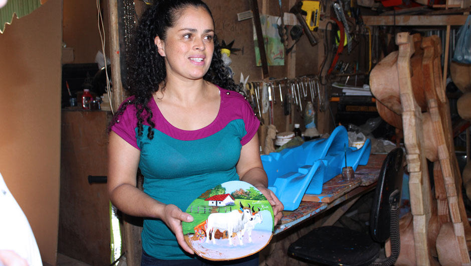 A smiling woman artisan displays a meticulously painted handicraft she created.