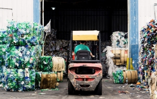 A man driving a forklift sorts recycling in a warehouse