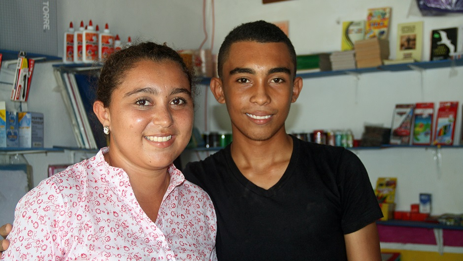 Two Colombia youth work at a small shop
