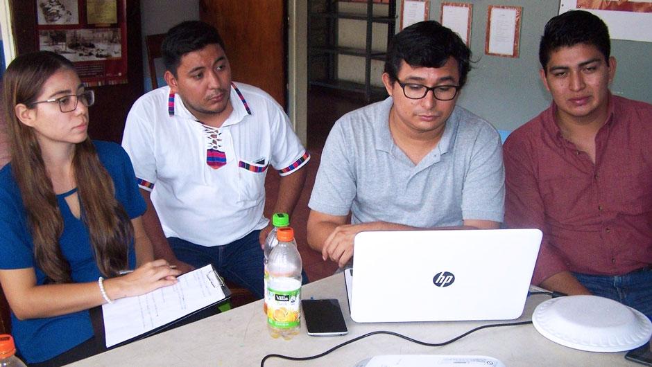4 Salvadoran young adults huddle around a computer screen