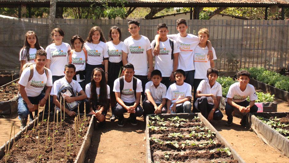 Young participants in the Huerto Escolar pose next to plants in their urban garden.