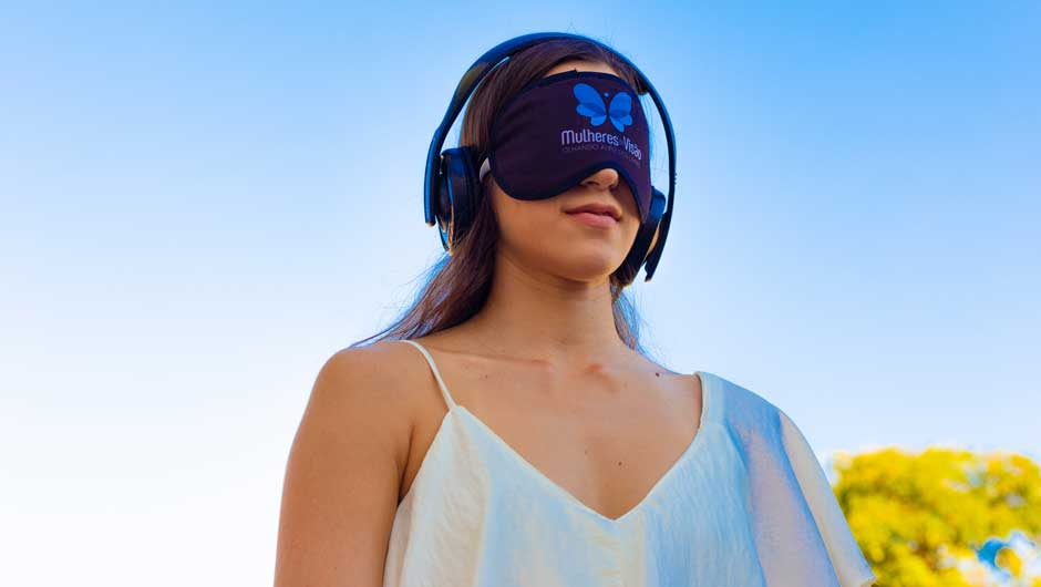 A young woman with a mask covering her eyes tests audio equipment to help visually impaired users.