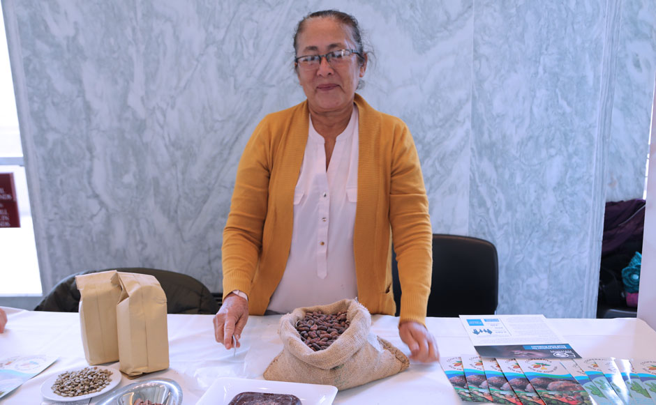 A cacao producer displays her product and educational information at an event.