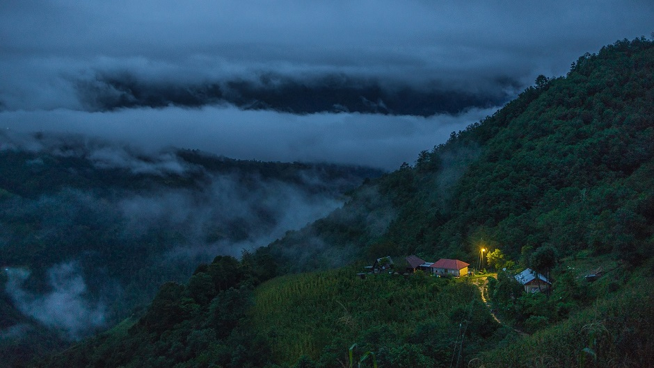 A small house is illuminated against a backdrop of a mountain and soaring clouds.