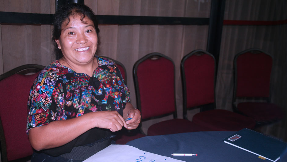 A smiling indigenous woman holds a marker to write down ideas during a group activity.up