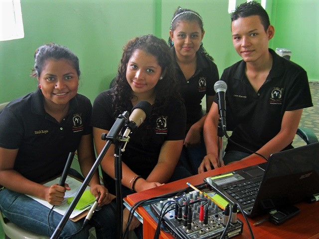 A group of 4 Honduran young people at work inside a recording studio.