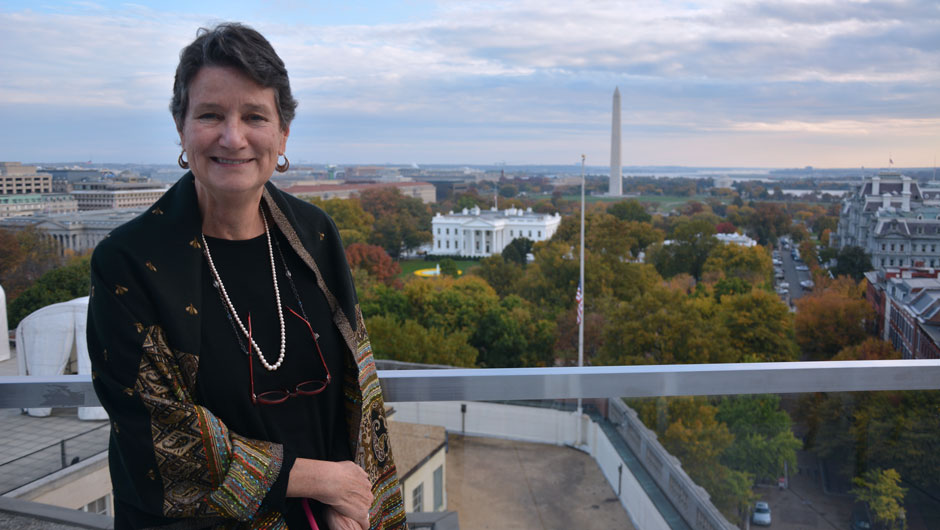 Marcy Kelley stands on the roof of a building with the White House and Washington Monument behind her.