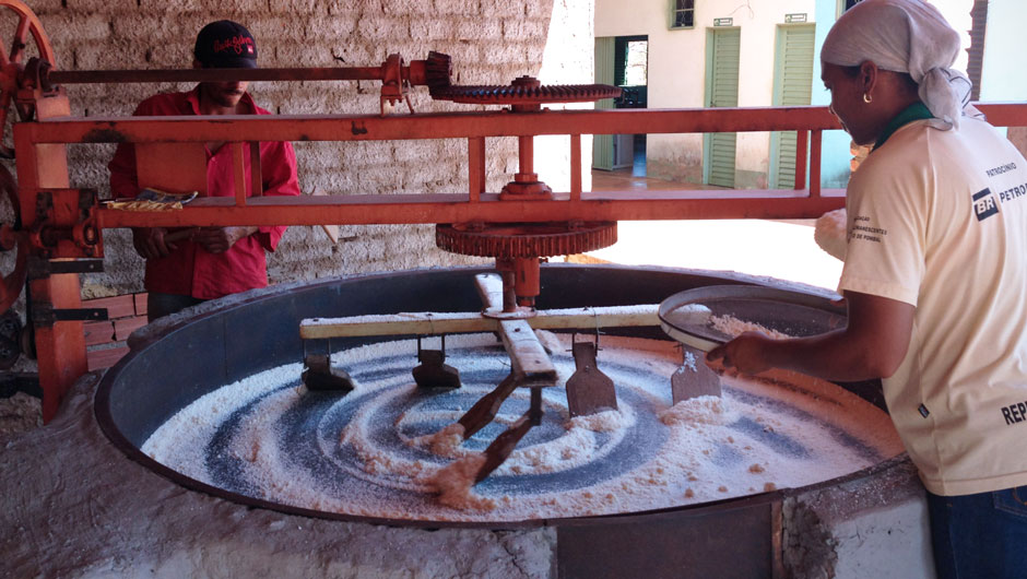 Two quilombola women use traditional flour mills to make flour from manioc.
