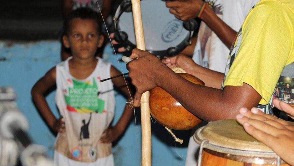 Músicos quilombolas tocan instrumentos tradicionales mientras un niño los mira.