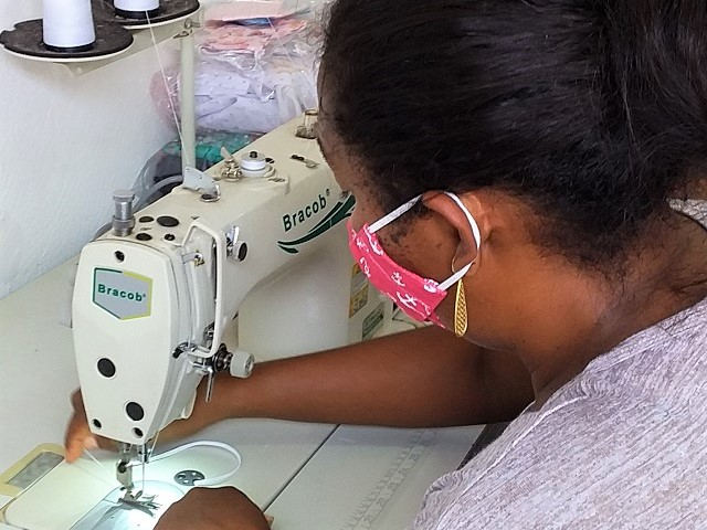 A Brazilian woman is wearing a handmade mask and sewing a different mask.