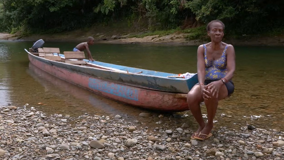 An elderly Afro-Colombian sits on the edge of a long canoe.