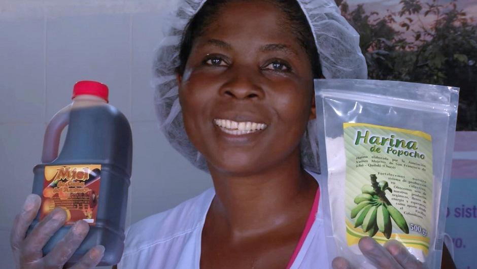 A young Afro-Colombian proudly holds up locally-made honey and flour.