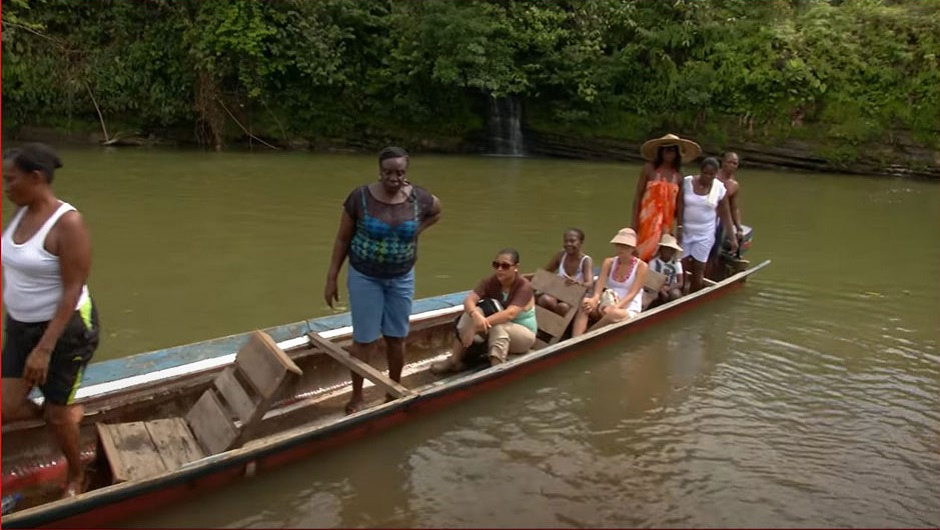 A group of Afro-Colombian women ride down a wide river in a canoe.